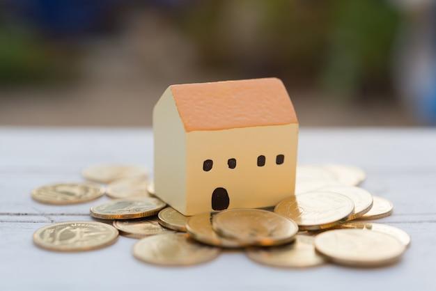 Huis en gouden munten op houten tafel met wazig aard, eigenschappen concept
