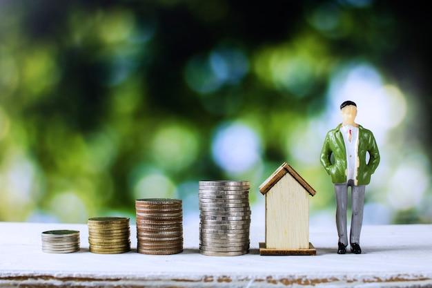 Huis en onroerende goederenconcept, bedrijfsmens die zich met gestapeld van muntstukken en huis bevindt