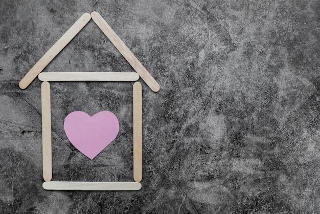 Huis gemaakt van houten ijs-sticks met hart vorm op zwarte grunge muur