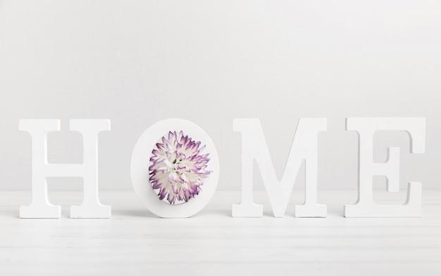 Huis geschreven met witte letters en mooie bloem