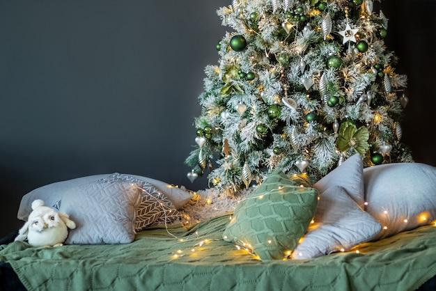 Huis gezellig interieur met kussens verspreid onder de sierlijke versierde kerstboom