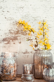 Huis gezellig mooi decor, verschillende vazen en kaarsen met lentebloemen, op een houten achtergrond, het concept van interieurdetails
