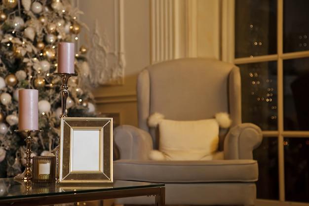 Huis gezellige kerst en gelukkig nieuwjaar interieur in woonkamer met kerstboom, een fauteuil en frame om op tafel te schrijven. achtergrond in vintage avondstijl met kopieerruimte. concept van vieren