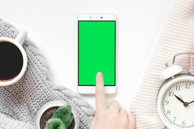Huis gezellige mockup sjabloon met een mobiele telefoon met groen scherm klok en gebreide vrouwen