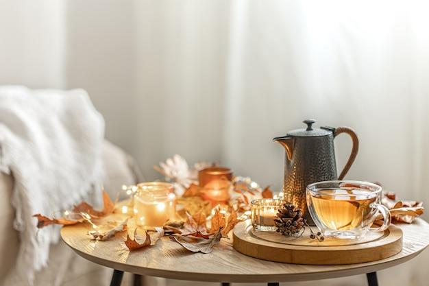 Huis herfst compositie met thee, droge bladeren en brandende kaarsen op onscherpe achtergrond, kopieer ruimte.