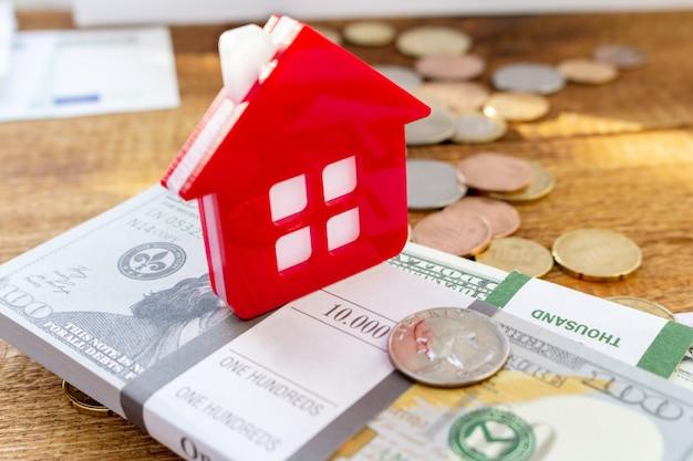 Huis huis op de bankbiljetten en munten achtergrond. onroerend goed kopen, onroerend goed kosten concept