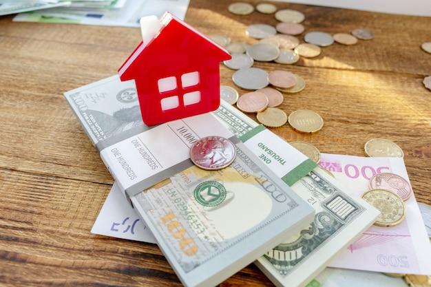 Huis huis op de bankbiljetten en munten achtergrond