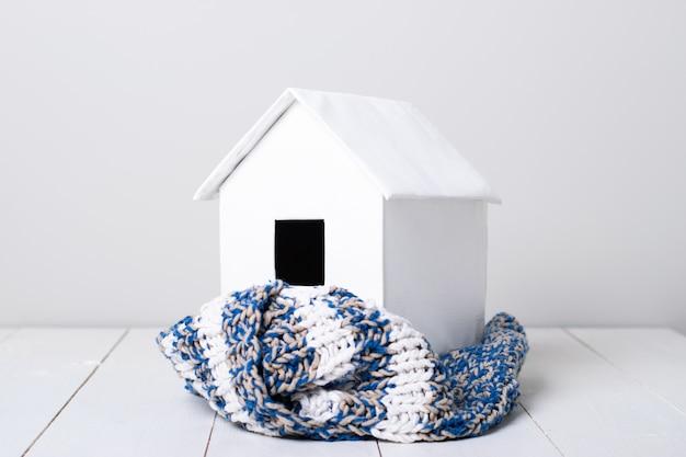 Huis in de winter - model van een huis dat een gebreide sjaal draagt