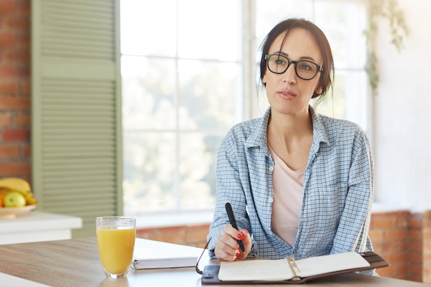 Huis interieur. aantrekkelijke vrouw draagt vrijetijdskleding, plan in dagboek schrijft, heeft peinzende uitdrukking