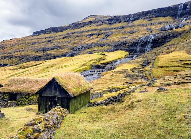 Huis met dak van gras. saksun-dorp en kleine watervallen. island streymoy, faeröer