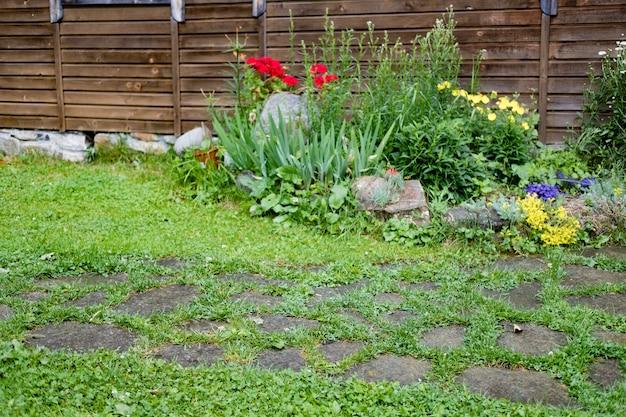 Huis met lelies, rozen, asters en andere bloemen
