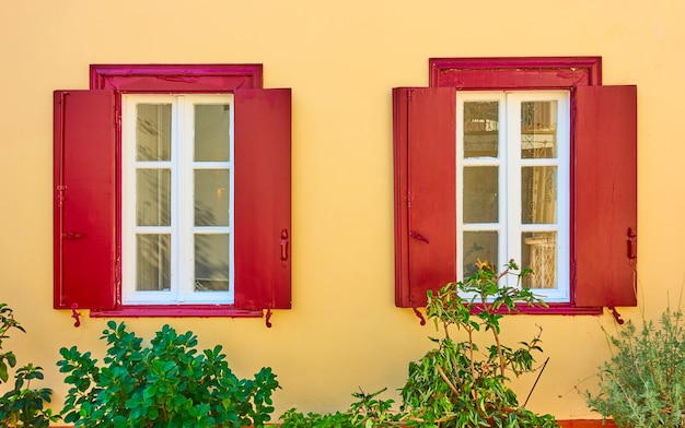 Huis met twee ramen met luiken in de wijk plaka in athene, griekenland