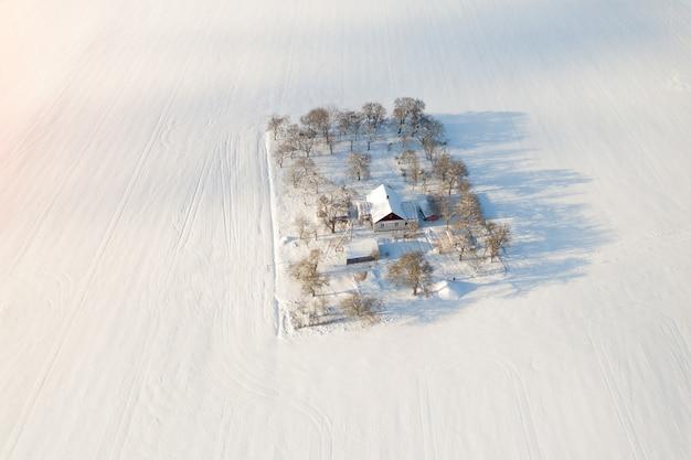 Huis midden in een sneeuwveld bovenaanzicht.