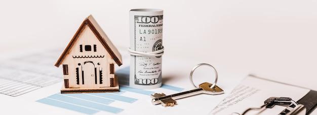 Huis miniatuurmodel en geld op documenten