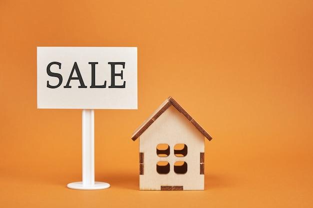 Huis model en teken verkoop op een bruine achtergrond kopie ruimte huis te koop