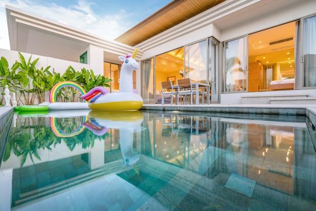 Huis of huis exterieurontwerp dat tropische poolvilla met groenentuin, zonbed, paraplu, zwembadhanddoeken en kleurrijke drijvende eenhoorn toont