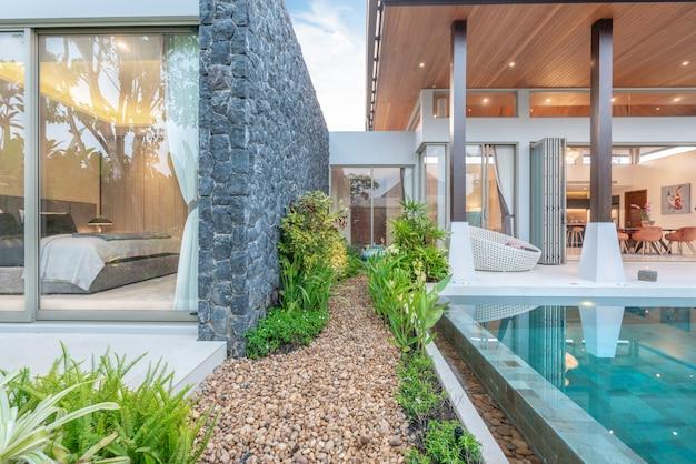 Huis of huis exterieurontwerp dat tropische poolvilla met groentuin en slaapkamer toont