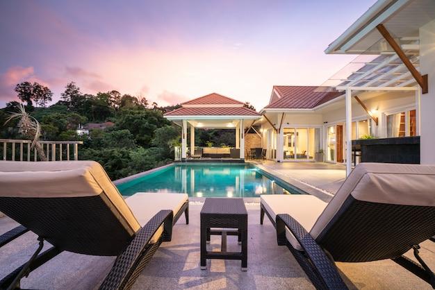 Huis of huis exterieurontwerp dat tropische poolvilla met zonbed toont