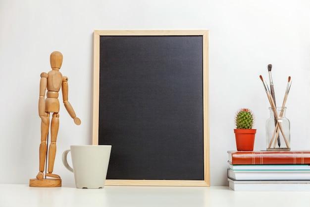 Huis of kantoor decor met lege schoolbord op tafel in de buurt van witte muur