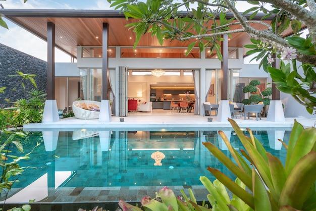 Huis- of woningbouw buiten- en binnenhuisarchitectuur met tropische zwembadvilla met groene tuin