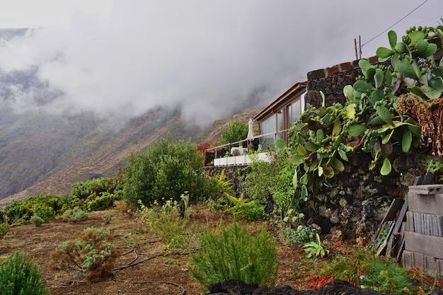 Huis omgeven door cactussen en verscholen in de berg midden in de mist. fronteravalley, eiland el hierro, canarische eilanden, spanje.
