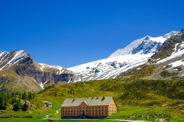Huis omgeven door rotsachtige bergen bedekt met groen en sneeuw in wallis in zwitserland