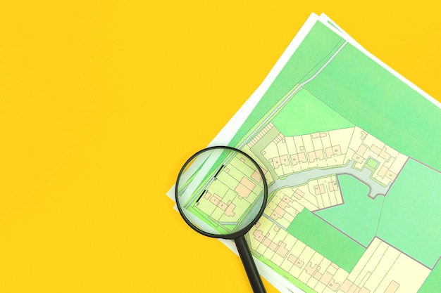 Huis onroerend goed audit en aankoop concept plat lag achtergrond, kadastrale kaart met vergrootglas erop, bovenaanzicht, bouwgrond foto