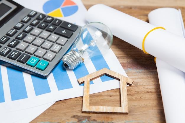 Huis, rekenmachine, gloeilamp en statistieken op houten tafel