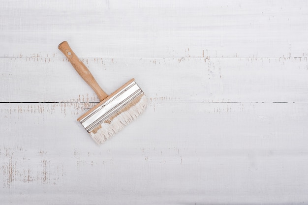 Huis renovatie concept. penseel met verf op een witte shabby houten achtergrond met kopie ruimte