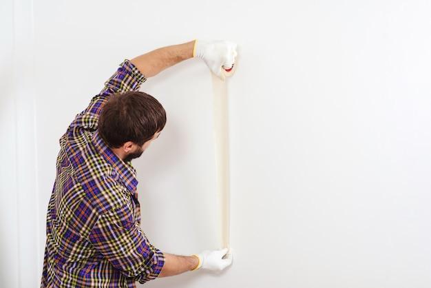 Huis renovatieservice. schilder die afplakband gebruikt alvorens te schilderen. schilder man aan het werk.