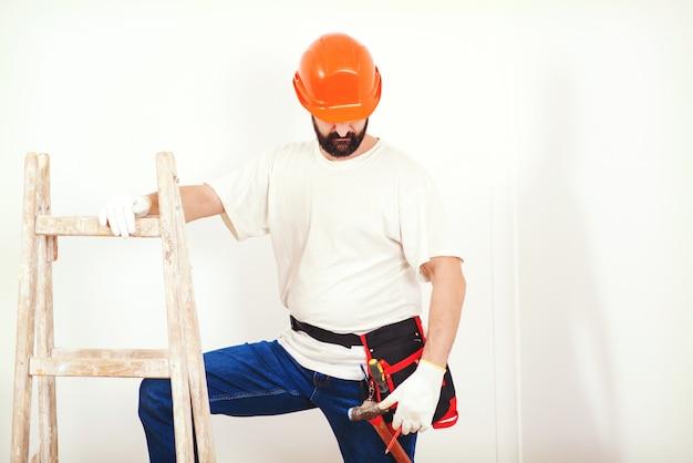 Huis renovatieservice. schilder man aan het werk. klusjesman met een gereedschapsriem.