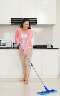 Huis schoonmaak service vrouw met dweil schoonmaak vloer in de keuken