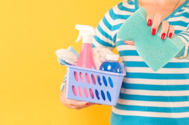 Huis schoonmaken concept. opruimingsservices. vrouw met mand met benodigdheden en spons.