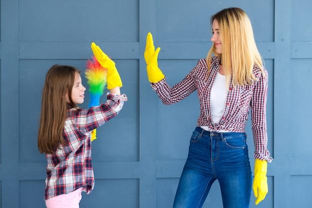 Huis schoonmaken en huishoudelijke taken. moeder en kind dochter geven high five.