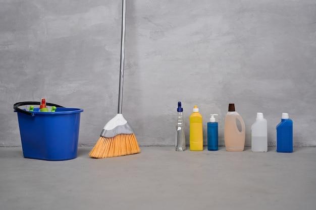 Huis schoonmaken en ontsmetten. plastic emmer met schoonmaakproducten, bezem, flessen met verschillende wasmiddelen die op de vloer staan tegen de grijze muur. huishoudelijk werk, schoonmaken, huishouden