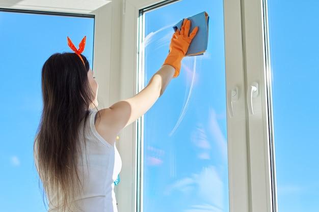 Huis schoonmaken, jonge mooie vrouw in handschoenen met wasmiddel en doek wassen ramen