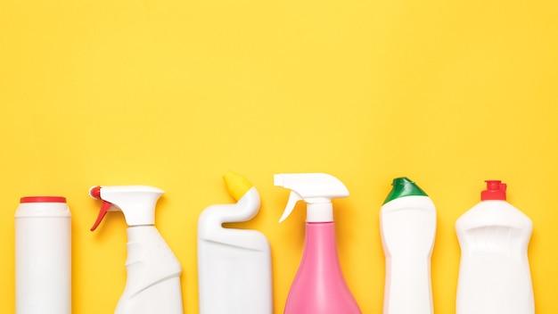 Huis schoonmakende levering op geel. rij van plastic flessen