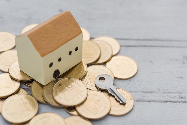 Huis, sleutel en gouden munten op houten tafel, eigenschappen concept