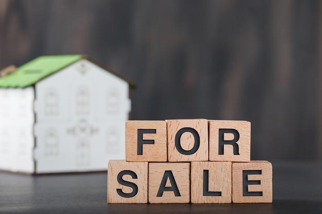 Huis te koop concept met houten kubussen, huismodel grijs.