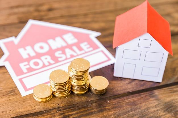 Huis te koop pictogram met gestapelde munten en huis op bureau