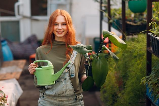 Huis tuinieren concept jonge vrouw met groene gieter planten bloemen in serre tuin thuis