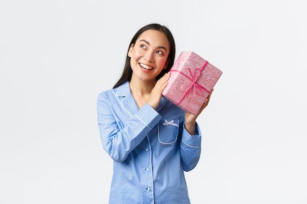Huis, vakantie en lifestyle concept. geïntrigeerd gelukkige verjaardag meisje in blauwe pyjama schuddoos met cadeau om erachter te komen wat erin zit, het heden raden en lachende nieuwsgierige, witte achtergrond