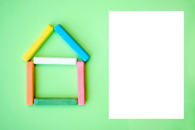 Huis van kleurpotloden en een wit blanco papier