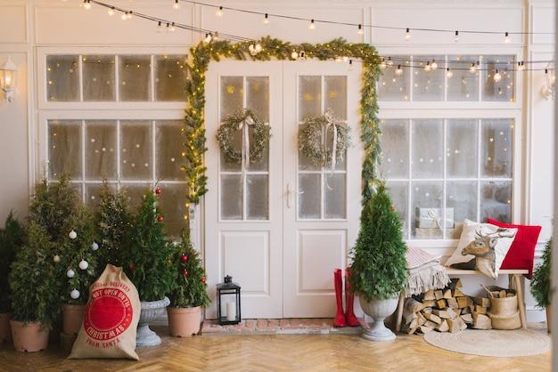 Huis versierd met kleine kerstbomen en lantaarns