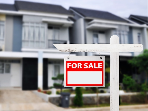 Huis voor verkoopraad met huisachtergrond