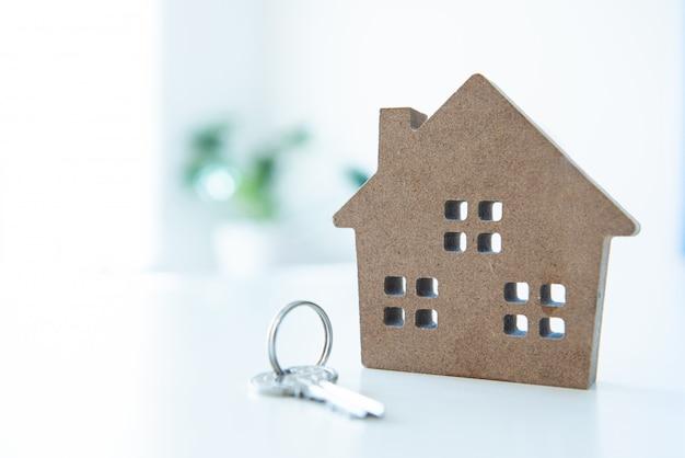 Huis vorm speelgoed met sleutelhanger op witte tafel en lege achtergrond.