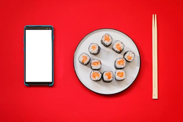Huis vorm sushi rolt met stokjes en smartphone op rode achtergrond