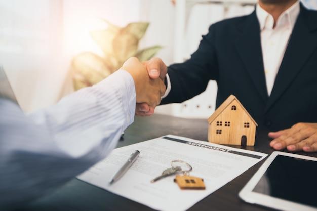 Huisagent schudt de hand van de klant na het contract ondertekenen