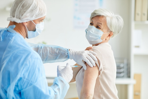 Huisarts draagt beschermend uniform injectie met coronavirusvaccin geven aan onherkenbare senior vrouw in schouder