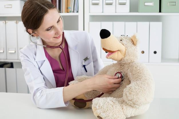 Huisartsonderzoek. mooie glimlachende vrouwelijke arts in witte jas onderzoekt teddybeer met een stethoscoop om het kind te kalmeren en te interesseren. spelen met babypatiënt. kindergeneeskunde medische concept